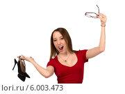 Радостная молодая женщина в красном платье с туфлями и очками в руках на белом фоне. Стоковое фото, фотограф Natalia Bogdanova / Фотобанк Лори