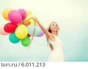 Купить «Красивая блондинка в белом летнем платье держит в руках много разноцветных воздушных шаров», фото № 6011213, снято 14 июля 2013 г. (c) Syda Productions / Фотобанк Лори