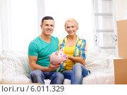 Купить «Мужчина и женщина со свиньей-копилкой в руках сидят на диване в новой квартире», фото № 6011329, снято 16 февраля 2014 г. (c) Syda Productions / Фотобанк Лори