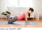 Купить «Фитнес дома. Девушка в спортивной форме выполняет упражнения на отжимание, лежа на коврике», фото № 6011397, снято 1 апреля 2014 г. (c) Syda Productions / Фотобанк Лори