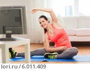 Купить «Занятия фитнесом перед телевизором дома. Девушка выполняет наклоны, сидя на полу», фото № 6011409, снято 1 апреля 2014 г. (c) Syda Productions / Фотобанк Лори