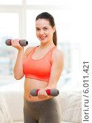 Купить «Девушка выполняет упражнения с легкими гантелями», фото № 6011421, снято 1 апреля 2014 г. (c) Syda Productions / Фотобанк Лори