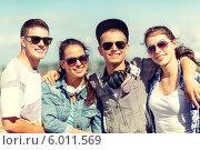 Купить «Улыбающиеся молодые люди в солнцезащитных очках стоя, обняв друх друга за плечи», фото № 6011569, снято 20 июля 2013 г. (c) Syda Productions / Фотобанк Лори