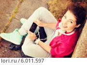 Купить «Девушка с наушниками и смартфоном сидит на траве около стены и смотрит вверх», фото № 6011597, снято 20 июля 2013 г. (c) Syda Productions / Фотобанк Лори