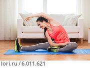 Купить «Привлекательная девушка занимается фитнесом в домашних условиях, сидя на полу на специальном коврике», фото № 6011621, снято 1 апреля 2014 г. (c) Syda Productions / Фотобанк Лори