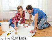 Купить «Молодые мужчина и женщина делают ремонт в новой квартире - наносят клей на обои», фото № 6011869, снято 26 января 2014 г. (c) Syda Productions / Фотобанк Лори