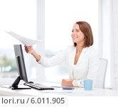 Купить «Молодая женщина с улыбкой протягивает документ, сидя за столом в офисе», фото № 6011905, снято 18 июля 2013 г. (c) Syda Productions / Фотобанк Лори