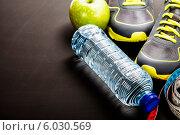 Купить «Спортивные кроссовки, бутылка воды и яблоко», фото № 6030569, снято 1 апреля 2014 г. (c) Наталия Кленова / Фотобанк Лори
