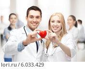 Купить «Два молодых врача-кардиолога держат в руках красное сердце», фото № 6033429, снято 18 мая 2013 г. (c) Syda Productions / Фотобанк Лори