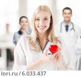 Купить «Медсестра с доброжелательной улыбкой держит в руках красное сердце», фото № 6033437, снято 18 мая 2013 г. (c) Syda Productions / Фотобанк Лори