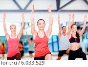 Купить «Радостные люди выполняют гимнастические упражнения в спортивном зале», фото № 6033529, снято 28 сентября 2013 г. (c) Syda Productions / Фотобанк Лори
