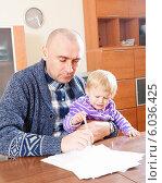 Купить «Молодой мужчина с дочерью на руках работает с документами дома», фото № 6036425, снято 4 апреля 2020 г. (c) Дарья Филимонова / Фотобанк Лори