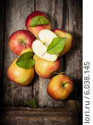 Купить «Яблоки с листьями на старом деревянном фоне», фото № 6038145, снято 24 июня 2014 г. (c) Наталья Осипова / Фотобанк Лори