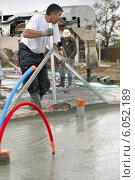 Купить «Workers pouring a cement foundation», фото № 6052189, снято 20 октября 2009 г. (c) Phovoir Images / Фотобанк Лори
