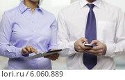 Купить «Two businesspeople with smartphone and tablet pc», видеоролик № 6060889, снято 20 декабря 2013 г. (c) Syda Productions / Фотобанк Лори