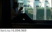 Купить «Женщина с чашкой сидит на окне на фоне современного города», видеоролик № 6094969, снято 29 мая 2014 г. (c) Данил Руденко / Фотобанк Лори
