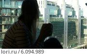 Купить «Женщина с чашкой сидит на окне на фоне современного города», видеоролик № 6094989, снято 29 мая 2014 г. (c) Данил Руденко / Фотобанк Лори