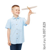 smiling little boy holding a wooden airplane model. Стоковое фото, фотограф Syda Productions / Фотобанк Лори
