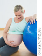 Купить «Smiling pregnant woman leaning against exercise ball holding her belly», фото № 6112385, снято 18 июля 2019 г. (c) Wavebreak Media / Фотобанк Лори