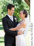 Newly wed couple embracing each other in garden. Стоковое фото, агентство Wavebreak Media / Фотобанк Лори
