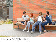 Купить «Students friends sitting bench outside campus», фото № 6134385, снято 19 июня 2014 г. (c) CandyBox Images / Фотобанк Лори