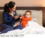 Купить «Young mother and her sick son in a bed», фото № 6140177, снято 10 мая 2014 г. (c) Andrejs Pidjass / Фотобанк Лори