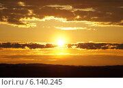 Солнце на закате среди золотистых облаков над чёрными силуэтами гор. Стоковое фото, фотограф Маркин Роман / Фотобанк Лори