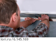 Купить «Tradesman laying down linoleum flooring», фото № 6145169, снято 30 ноября 2010 г. (c) Phovoir Images / Фотобанк Лори