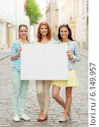 smiling teenage girls with blank billboard. Стоковое фото, фотограф Syda Productions / Фотобанк Лори