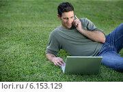 Купить «Relaxed man using phone and computer laid on the grass», фото № 6153129, снято 16 февраля 2008 г. (c) Phovoir Images / Фотобанк Лори