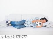 Football fan sleeping on couch hugging ball. Стоковое фото, агентство Wavebreak Media / Фотобанк Лори
