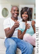 Купить «Happy couple relaxing on the couch having coffee», фото № 6182181, снято 19 февраля 2014 г. (c) Wavebreak Media / Фотобанк Лори
