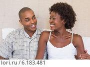 Купить «Happy couple sitting on bed smiling at each other», фото № 6183481, снято 14 марта 2014 г. (c) Wavebreak Media / Фотобанк Лори