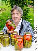 Купить «Женщина с консервированными овощами на дачном участке», фото № 6183761, снято 25 августа 2013 г. (c) Марина Славина / Фотобанк Лори