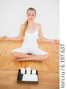 Купить «Peaceful blonde sitting in lotus pose on bamboo mat», фото № 6197637, снято 13 марта 2014 г. (c) Wavebreak Media / Фотобанк Лори