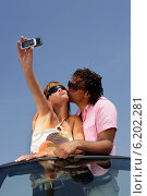 Funky couple in a convertible taking a photo on a cellphone. Стоковое фото, фотограф Phovoir Images / Фотобанк Лори