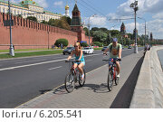 Купить «Молодые люди катаются на велосипедах по Кремлевской набережной в Москве», эксклюзивное фото № 6205541, снято 26 июля 2014 г. (c) lana1501 / Фотобанк Лори