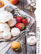 Купить «Десерт на серебряном подносе. Безе и клубника с абрикосами на деревянном столе», фото № 6227201, снято 22 мая 2014 г. (c) Natasha Breen / Фотобанк Лори