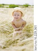 Купить «Забавный ребенок в шляпе стоит в траве ковыле», фото № 6229361, снято 25 мая 2008 г. (c) Владимир Сурков / Фотобанк Лори