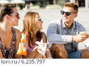 Купить «group of smiling friends sitting on city square», фото № 6235797, снято 20 июля 2014 г. (c) Syda Productions / Фотобанк Лори