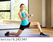 Купить «smiling woman with dumbbells in gym», фото № 6243941, снято 7 июня 2014 г. (c) Syda Productions / Фотобанк Лори