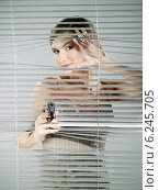 Купить «Woman's portrait while taking a shoot out of the blinds», фото № 6245705, снято 23 марта 2019 г. (c) BE&W Photo / Фотобанк Лори