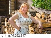 Купить «Рыжеволосая женщина среднего возраста стоит возле поленницы», фото № 6262997, снято 9 августа 2014 г. (c) Сергей Лаврентьев / Фотобанк Лори