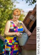 Купить «Рыжеволосая женщина средних лет стоит у колодца», фото № 6263141, снято 9 августа 2014 г. (c) Сергей Лаврентьев / Фотобанк Лори