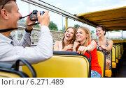 Купить «laughing friends with camera traveling by tour bus», фото № 6271489, снято 20 июля 2014 г. (c) Syda Productions / Фотобанк Лори