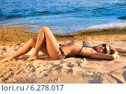 Сексуальная девушка в бикини лежит на морском пляже. Стоковое фото, фотограф Игорь Бородин / Фотобанк Лори