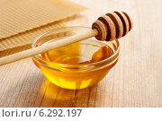 Купить «Bowl of honey and honeycomb in the background. Symbol of healthy living and natural medicine. Aromatic and tasty.», фото № 6292197, снято 22 апреля 2019 г. (c) BE&W Photo / Фотобанк Лори