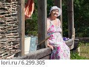 Купить «Пожилая женщина в летнем сарафане сидит на веранде деревенского дома», фото № 6299305, снято 31 июля 2014 г. (c) Кекяляйнен Андрей / Фотобанк Лори