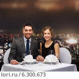 Купить «smiling couple holding hands at restaurant», фото № 6300673, снято 9 марта 2014 г. (c) Syda Productions / Фотобанк Лори