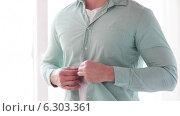 Купить «Close up of man unbuttoning his shirt at home», видеоролик № 6303361, снято 7 мая 2014 г. (c) Syda Productions / Фотобанк Лори